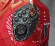O fim acima do farol dianteiro esquerdo do sp luxuoso vermelho Imagens de Stock Royalty Free