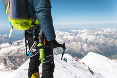 O fim acima do montanhista novo do indivíduo de A realiza em sua mão um gelo-machado que está em uma cimeira alta nas montanhas E fotografia de stock royalty free