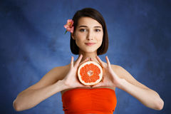 O fim acima do retrato da terra arrendada macia da moça cortou a laranja sobre o fundo azul Fotografia de Stock