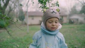 O fim acima do retrato do menino bonito da criança veste-se no revestimento do inverno, no lenço e nos flocos de neve do chapéu I vídeos de arquivo