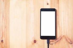 O fim acima do smartphone e o cabo de conexão dos dados para transferência e a bateria da carga no fundo e na textura de madeira  fotografia de stock royalty free