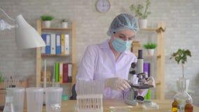 O fim acima do técnico de laboratório da mulher conduz a pesquisa usando um microscópio video estoque