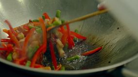 O fim acima do tiro do movimento lento que cozinha legumes frescos na frigideira quente, adiciona-os às batatas pre-brindadas