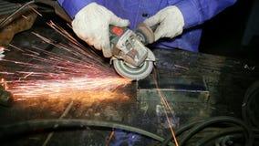 O fim acima do trabalhador do tiro com moedor mói o metall com faíscas video estoque