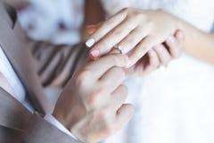 O fim acima dos pares do noivo da mão pôs a doação da aliança de casamento sobre a noiva imagem de stock