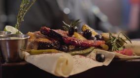 O fim acima dos peixes grelhados dos salmões serviu com os molhos, as ervas, as azeitonas, a pimenta de pimentão, o cal e o limão filme