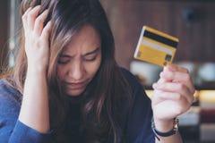 O fim asiático da mulher seus olhos ao guardar o cartão de crédito com sentimento forçado e quebrou foto de stock