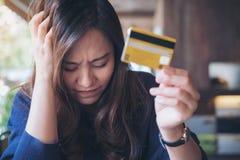 O fim da mulher seus olhos ao guardar o cartão de crédito com sentimento forçado e quebrou imagens de stock royalty free