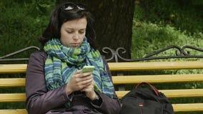 O fim disparou acima de um banco de parque e da mulher que sentam e que usam o telefone celular video estoque