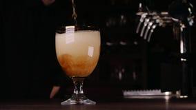 O fim disparou acima de um barman que derrama um vidro da cerveja video estoque