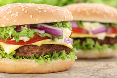 O fim do close up do hamburguer do Hamburger do cheeseburger acima dos tomates da carne deixou Foto de Stock
