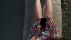 O fim do detalhe disparado acima de uma jovem mulher dedicada forma que usa seu telefone - texting e mensagem - veste o revestime video estoque