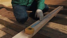 O fim equipa acima as mãos nas luvas que medem a prancha de madeira com régua, pôs uma marca do lápis video estoque