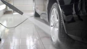 O fim levanta o tiro de um homem que usa o jato de água de alta pressão para lavar o carro em um carwash video estoque