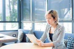 O financeiro fêmea está lendo notícias financeiras no Internet através da almofada de toque durante a ruptura de trabalho no café imagens de stock