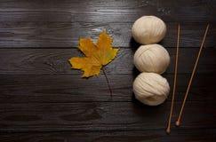 O fio branco, agulhas de confecção de malhas de madeira, amarelo sae na tabela escura Foto de Stock