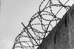 O fio de metal farpado gasto preto em fios em um muro de cimento cinzento contra um céu cinzento Pequim, foto preto e branco de C imagem de stock royalty free