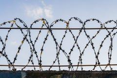 O fio de metal farpado gasto preto em fios em uma cerca contra um céu azul fotos de stock royalty free