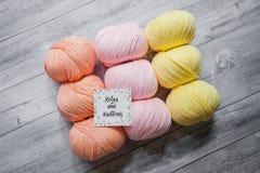 O fio do pêssego, o cor-de-rosa e o amarelo com uma inscrição relaxa e fazer malha fotos de stock