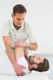 O fisioterapeuta masculino que estica a equipa a mão fotos de stock royalty free