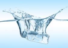 O flacon do champô hidratando, líquido cosmético, tônico cai na água azul com respingo grande da água Fotos de Stock Royalty Free