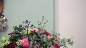 O florista Asian recolhe um grupo de rosas vermelhas, cor-de-rosa e brancas e de bagas vídeos de arquivo