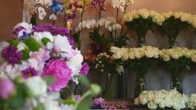 O florista bonito da menina faz a composição floral e sorri Negócio da flor Florista fêmea que faz o ramalhete bonito em filme