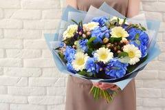O florista com um ramalhete bonito das mãos das flores imagem de stock