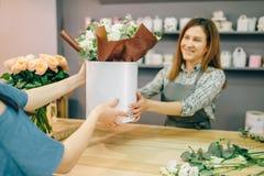 O florista dá a composição da flor ao cliente Imagem de Stock Royalty Free