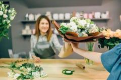 O florista dá o ramalhete fresco ao cliente fêmea Foto de Stock