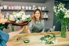 O florista dá o ramalhete fresco ao cliente fêmea Imagem de Stock Royalty Free