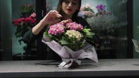 O florista da mulher na loja floral toma de flores pequenas no potenciômetro embalado acima do papel cor-de-rosa filme