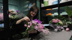 O florista de riso da mulher faz o ramalhete das tulipas, das rosas, das orquídeas e da solidago cor-de-rosa das flores video estoque