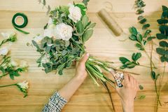 O florista entrega a composição da flor de cortes com tesoura de podar manual imagens de stock royalty free