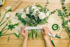 O florista entrega a composição da flor de cortes com tesoura de podar manual fotografia de stock