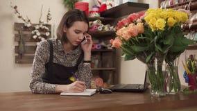O florista está falando no telefone, uma senhora comporá um ramalhete para o feriado filme