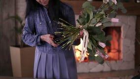 O florista fêmea corta as hastes das flores no ramalhete A mulher no vestido azul monta um ramalhete perfeito Toques finais video estoque