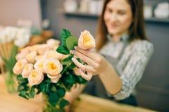 O florista põe rosas frescas em um vaso no florista Foto de Stock