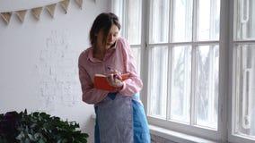 O florista profissional fala nas notas do telefone e da escrita ao caderno fotografia de stock royalty free