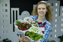 O florista smilling novo bonito da mulher está vendendo o bouqet das tulipas no florista imagem de stock royalty free