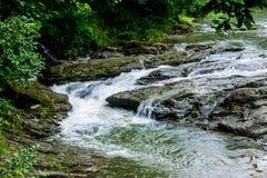 O fluxo da água em um rio da montanha com uma exposição de 1/15 de segundo fotos de stock royalty free