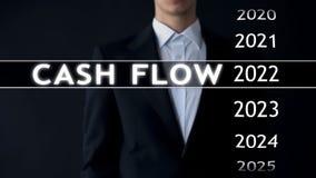 O fluxo de caixa para 2022, homem de negócios seleciona o relatório financeiro na tela virtual foto de stock royalty free
