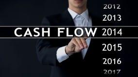 O fluxo de caixa para 2014, homem de negócios seleciona o relatório financeiro na tela virtual foto de stock
