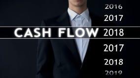 O fluxo de caixa para 2018, homem de negócios seleciona o relatório financeiro na tela virtual fotografia de stock
