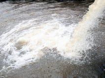 O fluxo para fora molha da canalização da fábrica industrial ao rio fotos de stock