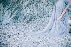 O foco das pedras bonitas, rochas no litoral, menina do disfocus em um vestido com a borda imagem de stock