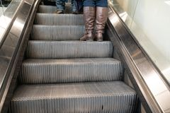 O foco macio na escadaria da escada rolante com as botas de couro marrons que estão na escadaria, os pés fêmeas do baixo tornozel fotografia de stock royalty free