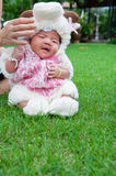 O foco no bebê recém-nascido asiático com os carneiros pequenos dos trajes no jardim e na mãe está guardando-a Fotografia de Stock