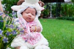 O foco no bebê recém-nascido asiático com os carneiros pequenos dos trajes no jardim e na mãe está guardando-a Foto de Stock