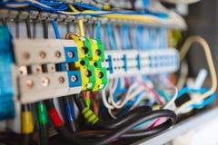 O foco seletivo de fios elétricos é conectado às braçadeiras do cuprum na caixa da distribuição de uma eletricidade no fotos de stock